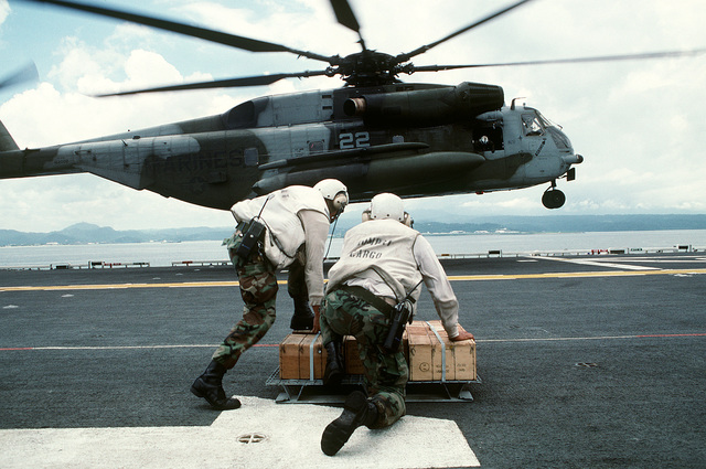 Two Marines assigned to the combat cargo office aboard the amphibious assault ship USS TARAWA (LHA-1) wait to carry a pallet of small arms ammunition onto a CH-53E Super Stallion helicopter during the combined Thai/U.S. joint Exercise Thalay Thai '89. The helicopter is assigned to Marine Medium Helicopter Squadron 163 (HMM-163), the reinforced aviation combat element of the 11th Marine Expeditionary Unit (11th MEU)