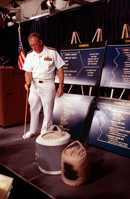 Rear Adm. Richard D. Milligan points to two powder bags during a Pentagon press conference called to release the findings of the Navy's official investigation into the April 19, 1989, explosion in Turret No. 2 aboard the battleship USS IOWA (BB-61). The powder bags are similar to those used aboard the IOWA at the time of the explosion. Behind the admiral are charts that detail the technical aspects of the investigation into the explosion