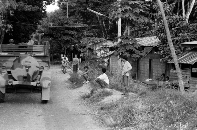 The residents of a village watch as a convoy of Marine Corps vehicles passes by during the combined Thai/U.S. Exercise Thalay Thai '89