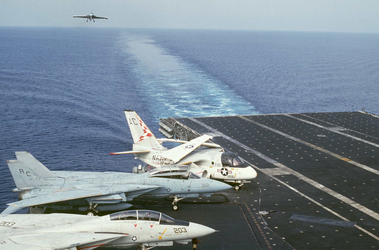 An A-6E Intruder aircraft comes in for a landing on the flight deck of the Aircraft Carrier USS JOHN F. KENNEDY (CV 67).  An S-3A Viking aircraft and two Fighter Squadron 32 (VF-32) F-14A Tomcat aircraft are parked on deck