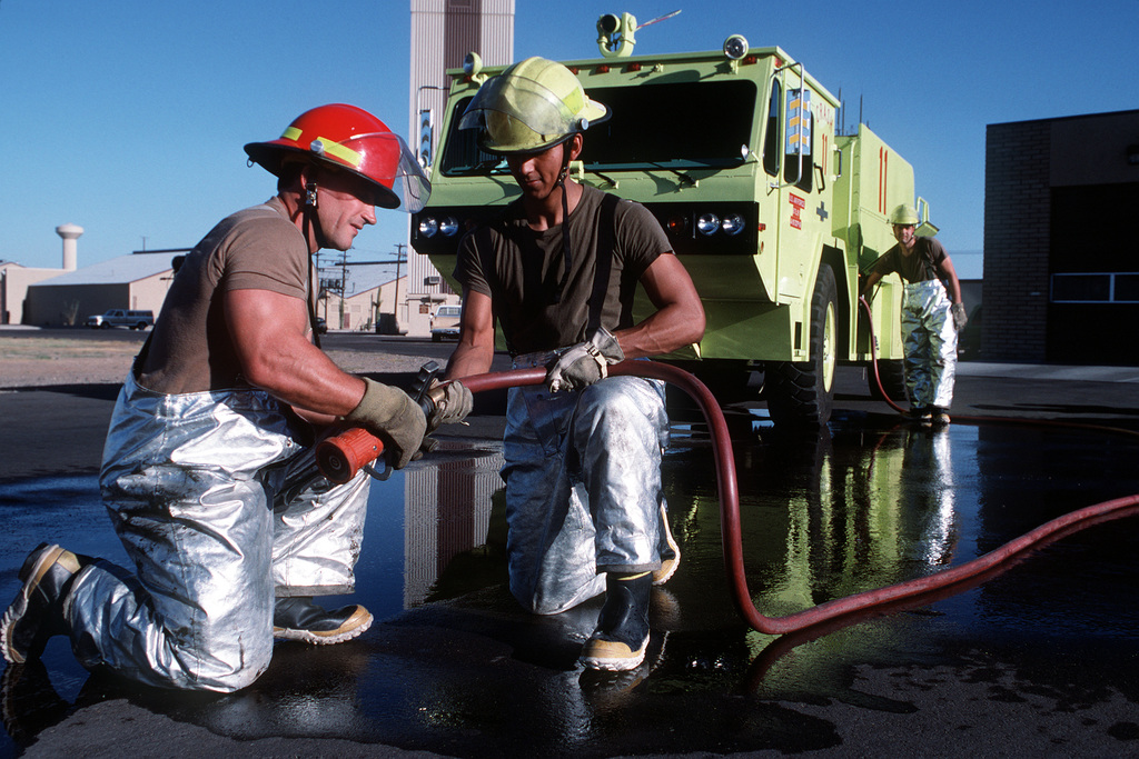 TSGT John R. Zarecor, SSGT Michael J. Rivera and SSGT Christopher A. Cole check the hose of a P-19A firefighting and rescue truck. The men are members of the Air Force Reserve's 944th Civil Engineering Squadron Fire Department