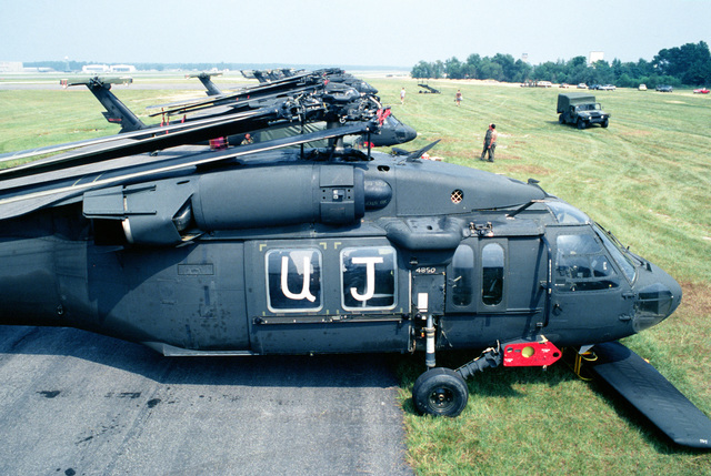 Several UH-60A Black Hawk helicopters, their main rotor blades folded back and their tailplanes removed, wait to be loaded aboard U.S. Air Force cargo aircraft during Exercise Market Square III. The helicopters are assigned to Co. A, 1ST Aviation Bn., 82nd Airborne Div