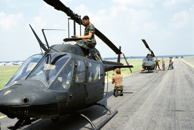 Soldiers from Co. A, 1ST Aviation Bn., 82nd Airborne Div. prepare two OH-58 Kiowa helicopters to be loaded aboard U.S. Air Force cargo aircraft during Exercise Market Square III
