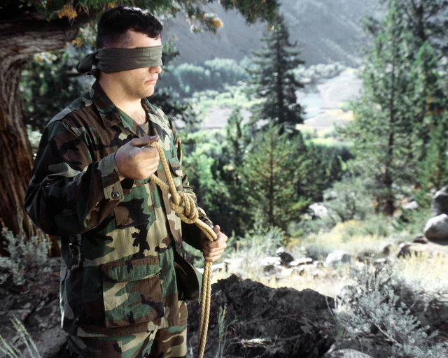 To increase his night proficiency, a member of the 3rd Battalion, 9th Marines, practices tying a knot blindfolded, during an exercise at the Mountain Warfare Training Center