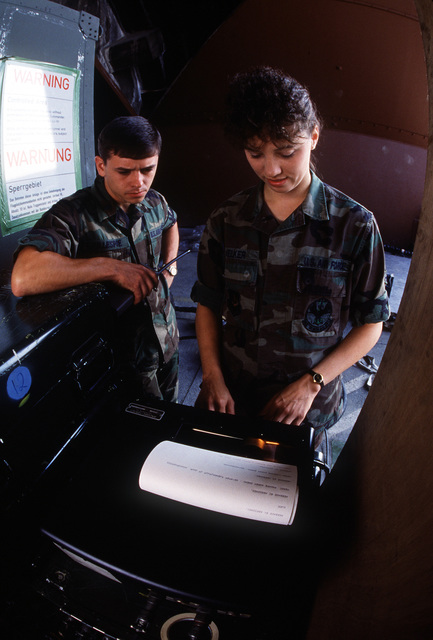 1LT Gallespie, officer in charge of the PHOTO Processing and Interpretation Facility deployed to Aviano, and SSGT Sharon Welker monitor the Tactical Electronic Reconnaissance (TEREC) remote terminal during Display Determination '89, a combined NATO exercise focusing on the defense of southern Europe