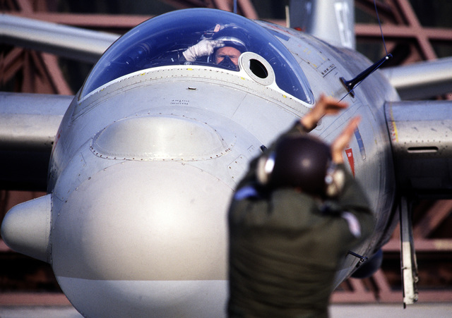 A ground crewman signals pilot LT Eddie Craig as he prepares his T. Mark 17 Canberra B. aircraft of the 360th Squadron for an electronic warfare training mission during Display Determination '89, a combined NATO exercise focusing on the defense of southern Europe