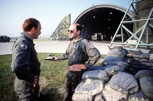 CPT Jeff Coombe, pilot, and CPT Duane Goehring, electronic weapons officer, confer before a mission during Display Determination '89, a combined NATO exercise focusing on the defense of southern Europe. Both men are members of the 42nd Electronic Combat Squadron