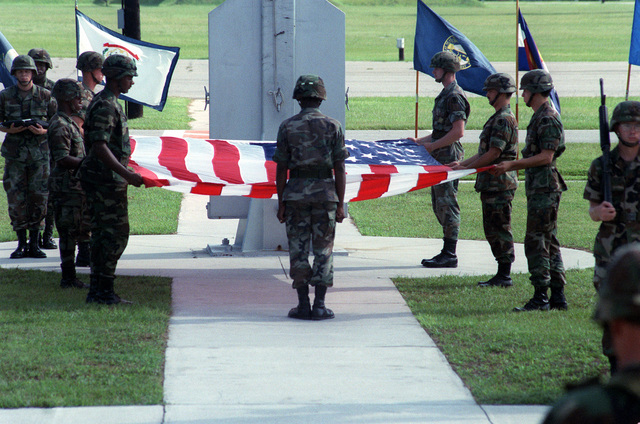 Soldiers of the 24th Infantry Division (Mechanized) prepare to fold the colors during a prisoner of war/mission in action (POW/MIA) retreat ceremony in front of Building 1
