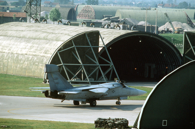 A 42nd Electronic Combat Squadron EF-111A Raven aircraft taxis between two hangars as it moves into position for takeoff during the U.S. Air Forces in Europe (USAFE) exercise Display Determination '89