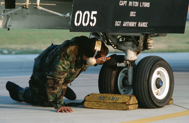 A member of the 42nd Aircraft Maintenance Unit checks the nose gear of a 55th Tactical Fighter Squadron F-111E aircraft during the U.S. Air Forces in Europe (USAFE) exercise Display Determination '89