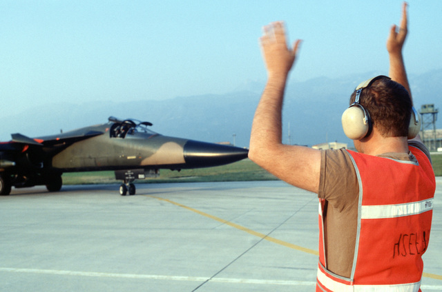 A member of the 42nd Aircraft Maintenance Unit signals to the pilot of a 55th Tactical Fighter Squadron F-111E aircraft that is taxiing to launch position during the U.S. Air Forces in Europe (USAFE) exercise Display Determination '89