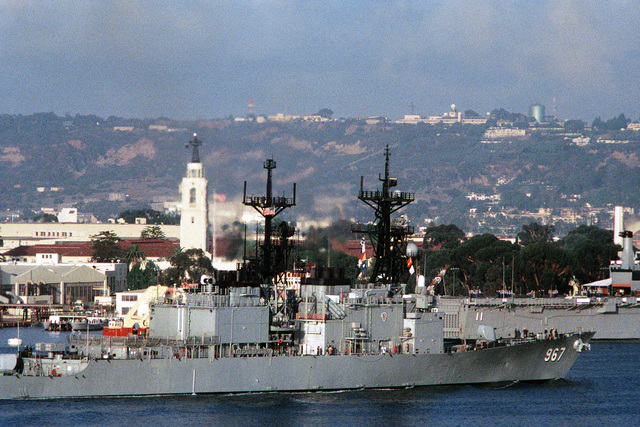 A starboard view of the destroyer USS ELLIOT (DD-967) departing port during PACEX '89