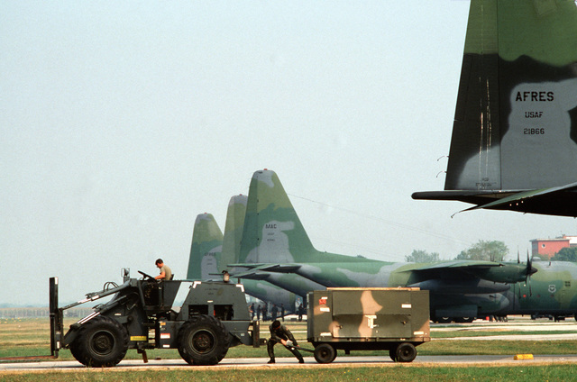 A trailer unloaded from a 317th Tactical Airlift Wing C-130E Hercules aircraft is pulled to the hitch on the back of an MW-20BFL forklift during the U.S. Air Forces in Europe (USAFE) exercise Display Determination '89
