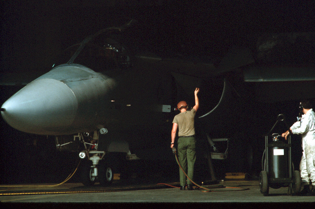A1C Richard L. Bigham, center, of the 42nd Aircraft Maintenance Unit prepares a 42nd Electronic Combat Squadron EF-111A Raven aircraft for flight during the U.S. Air Forces in Europe (USAFE) exercise Display Determination '89
