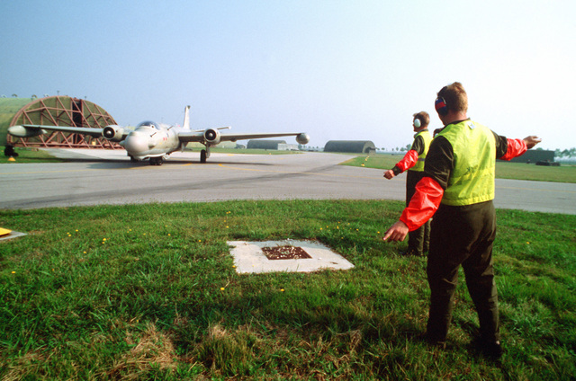 British airmen from the Royal Air Force's 360 Squadron direct a T. Mark 17 Canberra aircraft onto a taxiway during the U.S. Air Forces in Europe (USAFE) exercise Display Determination '89