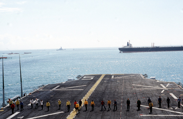 Crewmen aboard the amphibious assault ship USS PELELIU (LHA 5) spread out across the flight deck to search for objects that could cause foreign object damage (FOD) to helicopters landing aboard the ship. The PELELIU and its contingent of embarked Marines will be taking part in PACEX '89