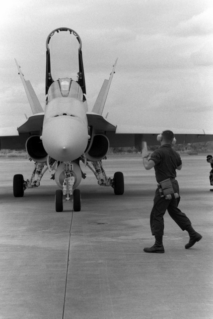 LCPL Steven Lyon, a plane captain with Marine Fighter Attack Squadron 115 (VMFA-115), directs a taxiing F/A-18A Hornet aircraft during the combined Thai/U.S. exercise Thalay Thai '89