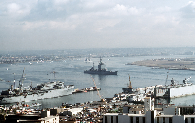 The nuclear-powered guided missile cruiser USS LONG BEACH (CGN 9) steams past the docked submarine tender USS DIXON (AS 37) during PACEX '89