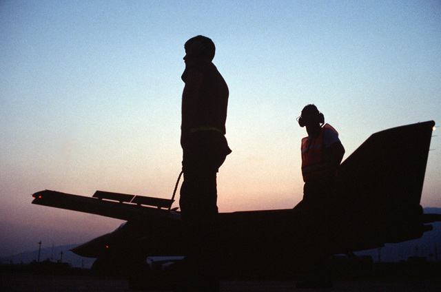 Two members of the 42nd Aircraft Maintenance Unit stand aside after performing a final pre-launch check on a 55th Tactical Fighter Squadron F-111E aircraft during the U.S. Air Forces in Europe (USAFE) exercise Display Determination '89