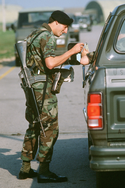 With an M-16A1 rifle slung over his shoulder, A1C Mark H. Hyden of the 40th Security Police Flight checks an entry authorization badge outside of the base's hardened operations area during the U.S. Air Forces in Europe (USAFE) exercise Display Determination '89
