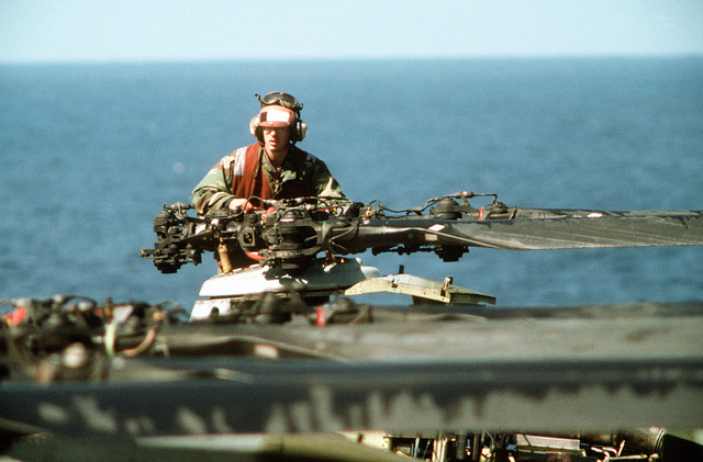 A flight deck crewman services the rotor hub of a helicopter during PACEX '89