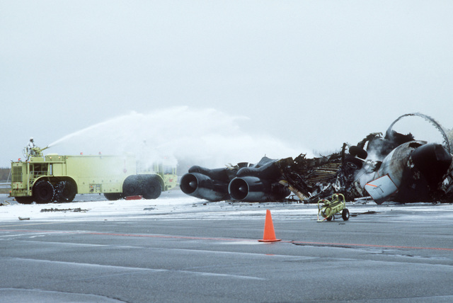 Crash crewmen aboard a P-15 aircraft firefighting and rescue truck spray a foam/water agent on the remnants of an Alaska Air National Guard KC-135E Stratotanker aircraft that exploded and burned while taxiing to a parking area. Two of the aircraft's seven crewmen were killed; the others sustained only minor injuries