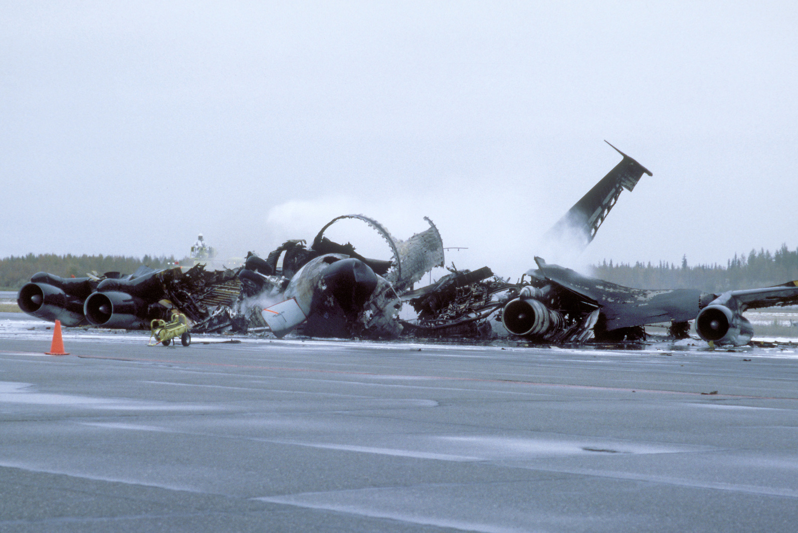 Crash crewmen spray a foam/water agent on the remnants of an Alaska Air National Guard KC-135E Stratotanker aircraft that exploded and burned while taxiing to a parking area. Two of the aircraft's seven crewmen were killed; the others sustained only minor injuries