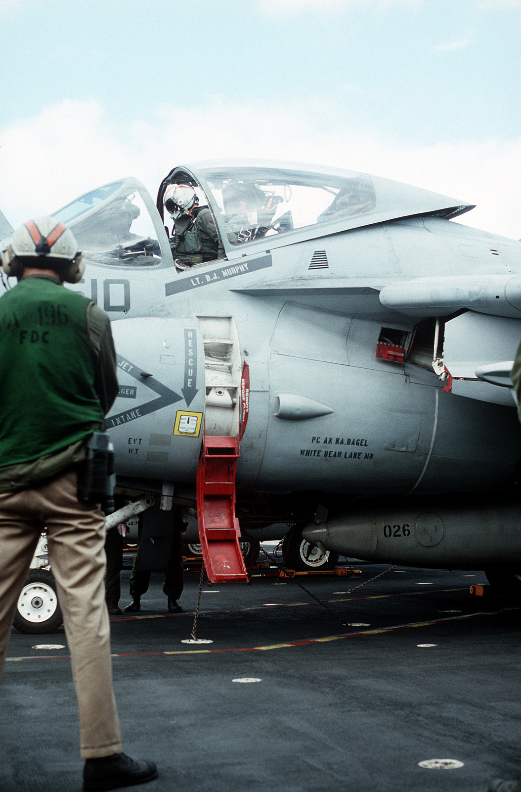 A catapult crew member stands by as the pilot closes the cockpit of an A-6E Intruder aircraft on the flight deck of the aircraft carrier USS Constellation (CV-64) during PACEX '89
