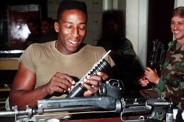 A Marine aboard the amphibious assault ship USS Peleliu (LHA-5) cleans an M-203 grenade launcher from his M-16A2 rifle during PACEX '89