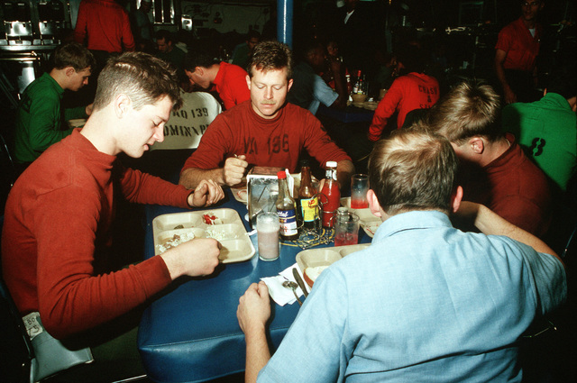 Flight deck crewmen aboard the aircraft carrier USS CONSTELLATION (CV 64) eat a meal during PACEX '89
