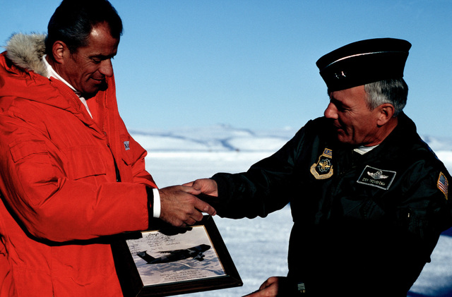 Major General Richard Trzaskoma, Commander, 22nd Air Force, presents a picture of one of the first C-5B Galaxy aircraft to land near McMurdo Station to Dr. Peter Wilkniss, Director, Division of Polar Programs, National Science Foundation. The Galaxy touched down on an ice runway, which is over 10,000 feet long and was scraped from ice over eight feet deep. The aircraft is at the station during Operation DEEP FREEZE '90