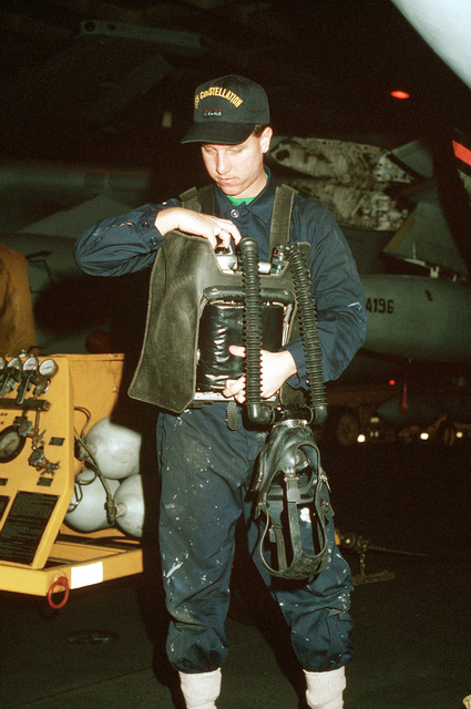 A sailor sets the timer on his oxygen breathing apparatus (OBA) prior to a hangar deck firefighting drill aboard the aircraft carrier USS CONSTELLATION (CV 64) during PACEX '89
