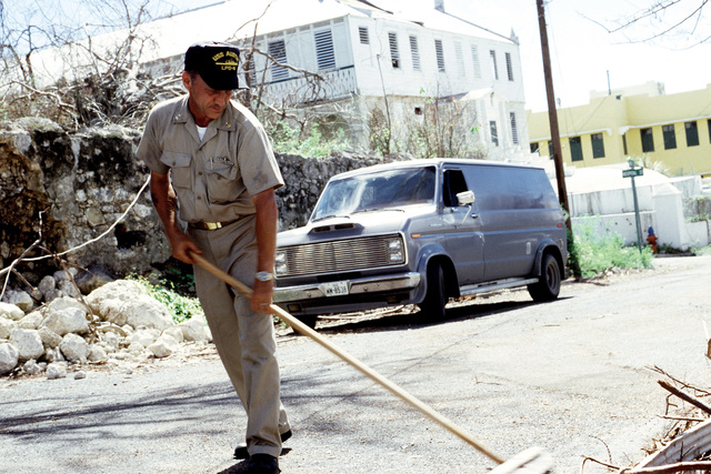 An officer from the amphibious transport dock USS AUSTIN (LPD 4) sweeps debris from a street during cleanup efforts in the aftermath of Hurricane Hugo, which devastated the area on September 19th