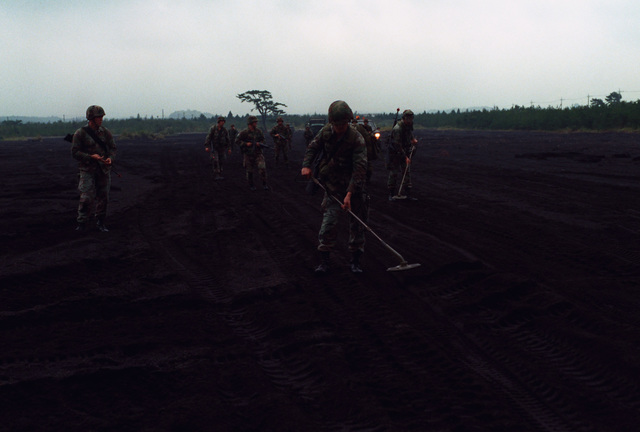 Two Marines of Marine Wing Support Squadron 171 (MWSS-171), 1ST Marine Aircraft Wing (1ST MAW), uses AN/PSS-11 metallic mine detectors to sweep a road during the squadron's battle skills testing