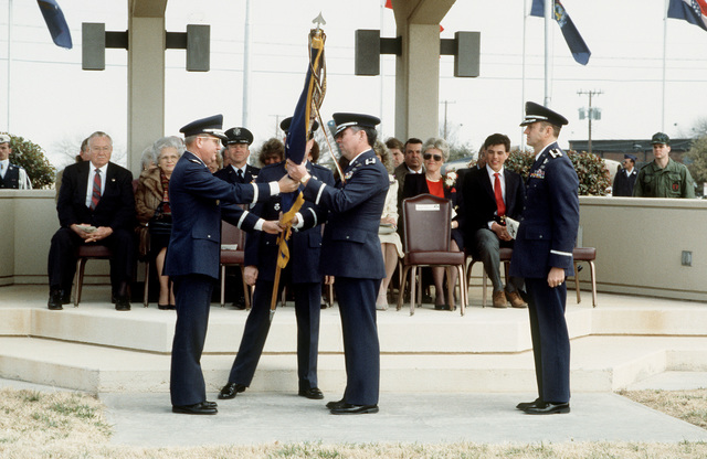 LGEN Richard A. Burpee, left, Commander, 15th Air Force, passes the unit colors to COL William J. Ehrie during the 96th Bombardment Wing (96th BMW) change of command ceremony. Ehrie is relieving COL Albert D. Jensen, right, as commander of the 96th BMW