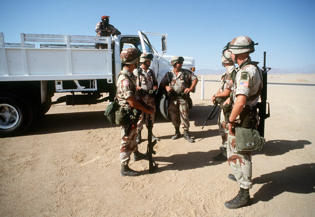 Several soldiers from the 82nd Airborne Division wait to board a truck prior to their shift on guard duty. The soldiers and their unit are serving as peacekeepers in the Sinai desert with the Multinational Force and Observers