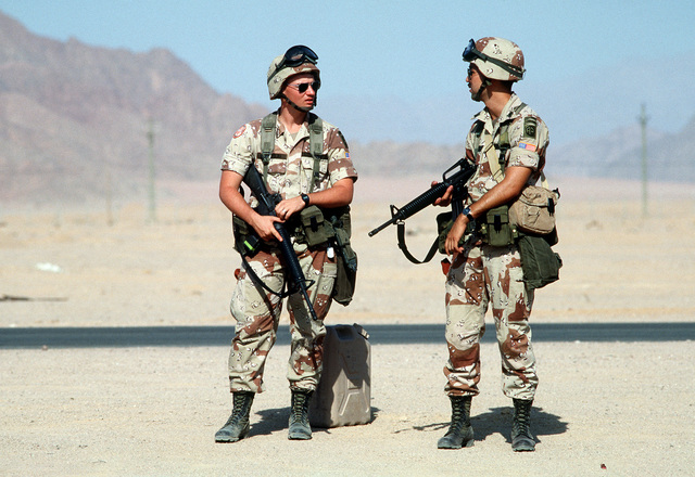 Two soldiers from the 82nd Airborne Division pause near a road during their shift on guard duty. The soldiers and their unit are serving as peacekeepers in the Sinai desert with the Multinational Force and Observers