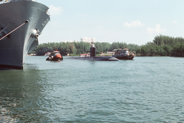 Commercial tugs escort the nuclear-powered attack submarine USS ALBUQUERQUE (SSN 706) as it arrives to take part in Navy Appreciation Week 1989, which is sponsored by the Port Everglades Authority, the Broward County community and the Navy League of the United States. At left is the amphibious command ship USS MOUNT WHITNEY (LCC 20)