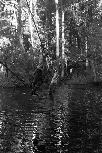 Members of the 3rd Light Anti-Aircraft Missile (3rd LAAM) Battalion cross a rope bridge over a water obstacle on the battlefield fitness course