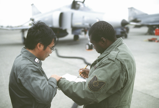 MSGT Willie Boyd, production supervisor with the 90th Aircraft Maintenance Unit, checks fuel records with a supply sergeant of the Japan Air Self Defense Force (JASDF) during exercise Cope North 90-1, a joint U.S. Air Force/JASDF exercise