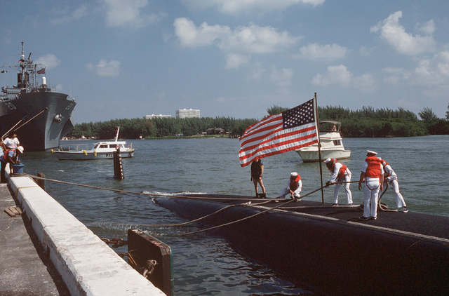 Sailors on the deck of the nuclear-powered attack submarine USS ALBUQUERQUE (SSN 706) take up slack in a line as the ALBUQUERQUE arrives to take part in Navy Appreciation Week 1989, which is sponsored by the Port Everglades Authority, the Broward County community and the Navy League of the United States