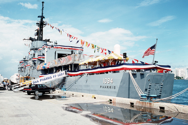 The frigate USS PHARRIS (FF-1094), decorated with bunting and a rainbow flag hoist, sits tied up at the pier during Navy Appreciation Week 1989, which is sponsored by the Port Everglades Authority, the Broward County community and the Navy League of the United States