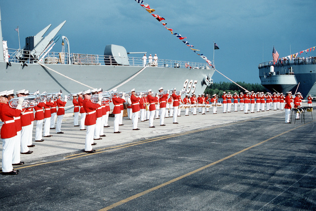 The US Marine Corps Drum and Bugle Corps plays on the pier in front of the guided missile destroyer USS SCOTT (DDG 995) during Navy Appreciation Week 1989, which is sponsored by the Port Everglades Authority, the Broward County community and the Navy League of the United States. The stern of the amphibious command ship USS MOUNT WHITNEY (LCC 20) is at left