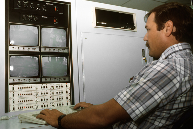 A technician operates a control panel that records the findings of the base's maneuverable X-ray machine. The 110-ton robot is one of two newly developed devices used to detect aircraft structural flaws