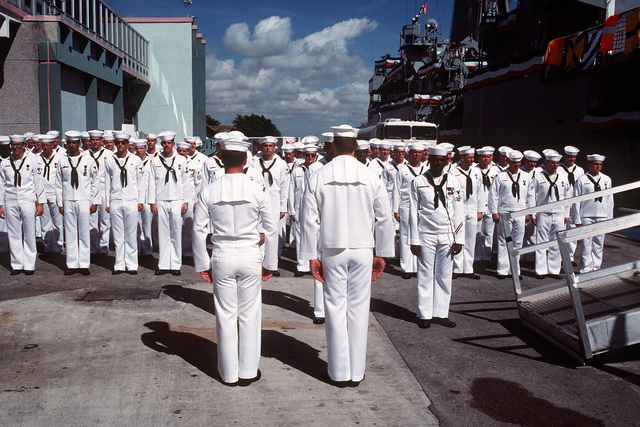 Crewmen stand at attention on the pier beside the frigate USS PHARRIS (FF-1094) for the ship's change of command ceremony. The ceremony is taking place during Navy Appreciation Week 1989, which is sponsored by the Port Everglades Authority, the Broward County community and the Navy League of the United States