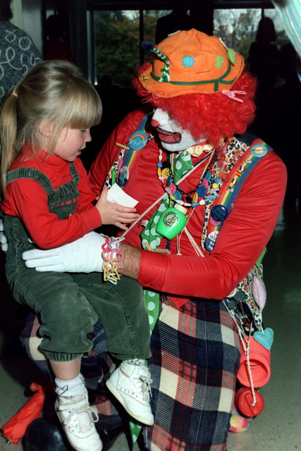 CHIEF Boatswain's Mate Frank Brant, dressed as Dr. Gadgets, entertains a child at Mercy Hospital. The chief petty officer who is stationed aboard the aircraft carrier USS JOHN F. KENNEDY (CV 67), spends many off-duty hours visiting schools, orphanages and hospitals