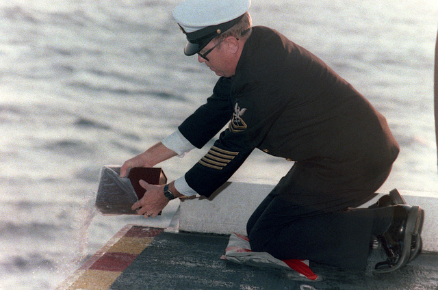 CHIEF Damage Controlman Sease commits the remains to the sea during a burial at sea service aboard the aircraft carrier JOHN F. KENNEDY (CV 67)