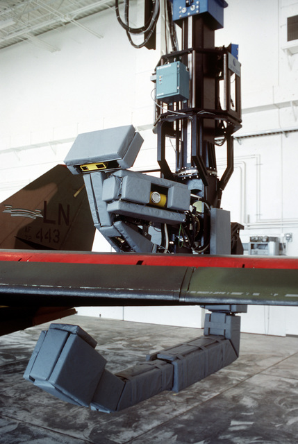 A maneuverable X-ray machine inspects the wing of an F-111 aircraft in the base's non-destructive inspection facility. The 110-ton robot is one of two newly developed devices used to detect aircraft structural flaws