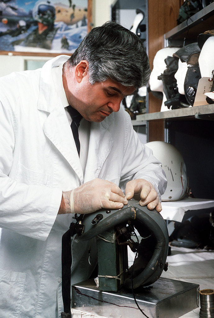 San Antonio Air Logistics Center. Mike Grost, chief investigator at the Life Support Equipment Investigation Laboratory, reassembles a flight helmet in an effort to determine the cause of an airplane crash. Grost analyzes flight gear, clothing, life support equipment and aircraft parts to determine the cause of plane accidents in the interest of preventing future tragedies