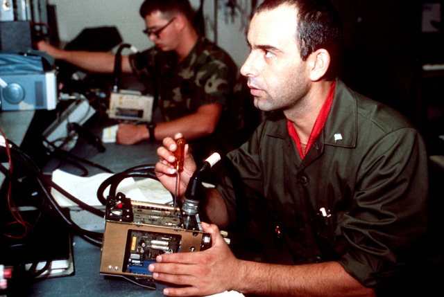 A student from the Greek armed forces glances at his diagnostic equipment as he repairs a CH-47C Chinook helicopter's automatic speed trim amplifier at the US Army Signal Center